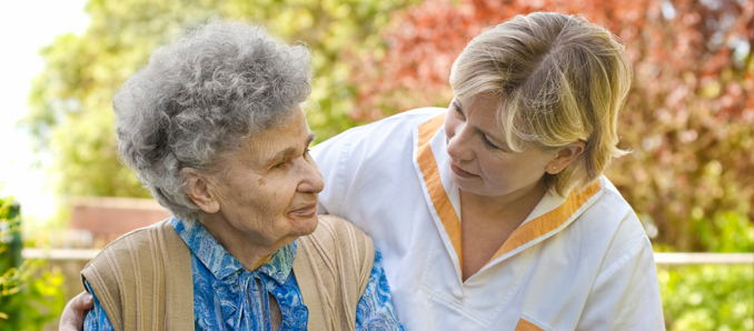 Elderly woman with a nurse outside